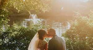Bride and groom kissing by lake with fountain