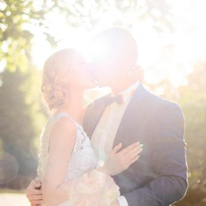 bride and groom kissing near a tree, leaves blurred above and behind them with the bright sun behind them.