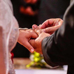 Groom placing ring on brides finger.