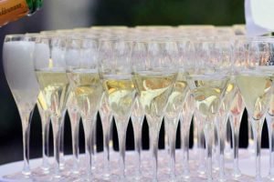 Many champagne flute glasses filled with champagne and bubbling standing very close together on a white table.