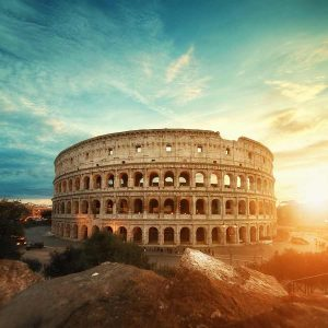 Romes Colosseum with sun behind it.