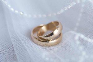 Two stacked wedding rings with decoration of veil and pearls beneath.