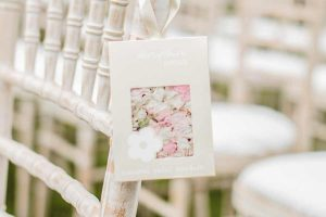 White wooden chairs with padded seats and rail backs and a sachet of flower petals hanging from the back left.
